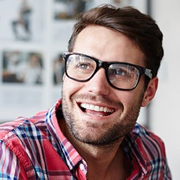 Man with spectacles smiling jovially