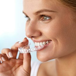 Woman placing an Invisalign tray