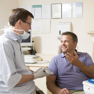 Smiling man in dental chair talking to dentist