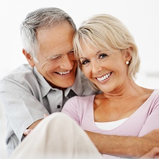 Older man and woman hugging and smiling