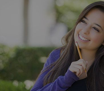 Student holding pencil to mouth smiling
