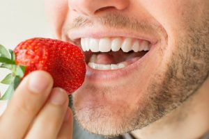 man eating strawberry with dental implants