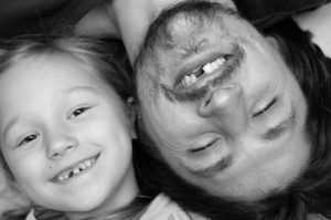 Smiling father and daughter both missing a front tooth