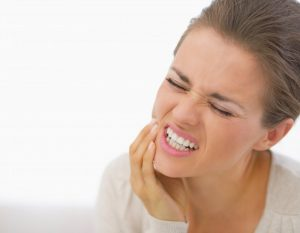 woman frowning holding jaw in pain