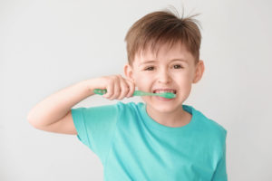 Child brushes teeth while away from a children's dentist.