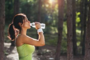 woman drinking water after intense exercise